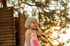 Young blonde child girl making a face outdoor with big tree on background. Warm sunset light. Family summer trave stock image