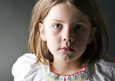 A young blonde child looks a the camera in concern Royalty Free Stock Photos