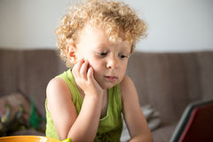 Young blonde child looks a tablet Stock Images