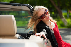 Young blonde with a convertible. Royalty Free Stock Images