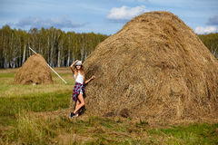 Young blonde country girl in hat near haystack Royalty Free Stock Image