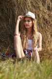 Young blonde country girl in hat near haystack Stock Photography