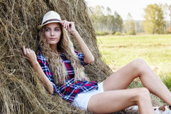 Young blonde country girl in hat near haystacks Stock Photo