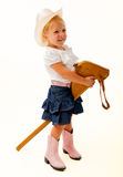 Cowgirl riding stick horse. Young blonde cowgirl in pink cowboy boots and hat riding a stick horse stock images