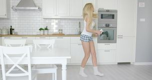 Young blonde dancing at home stock footage