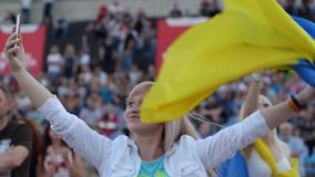 Young blonde is dancing waving Ukrainian flag at rock concert and takes herself off on smartphone, close-up, Beautiful stock footage