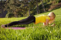 Young blonde doing plank exercise outdoors Stock Photo