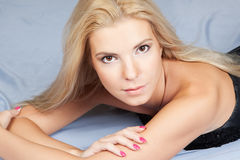 Young blonde fashion woman lying in studio Royalty Free Stock Photos