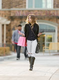 Young blonde female shopping with pink and red bags holding a cell phone Stock Images