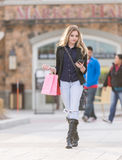 Young blonde female shopping with pink and red bags holding a cell phone Stock Photography