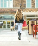Young blonde female shopping with pink and red bags holding a cell phone Royalty Free Stock Image