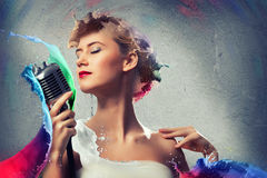 Young blonde female singer with microphone Stock Photography
