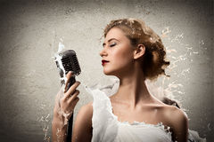 Young blonde female singer with microphone Royalty Free Stock Images