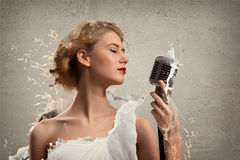 Young blonde female singer with microphone Royalty Free Stock Photos