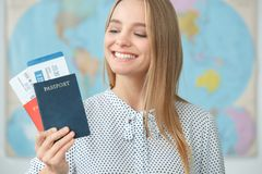Young blonde female traveler in a tour agency holding passports close-up. Young woman traveler in a tour agency standing holding passports smiling looking on the royalty free stock images