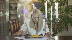 Blonde young female in white jacket eating italian cuisine pasta spaghetti alone in fancy restaurant making funny face. Young blonde female in white jacket stock footage