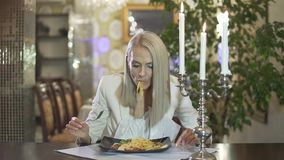 Young blonde female in white jacket eating italian cuisine pasta spaghetti alone in fancy restaurant making funny face. Young skinny blonde female in white stock video footage
