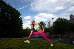 Young Blonde fit Athletic woman exercising in Park. Young Blonde fit Athletic woman exercising in Central Park Royalty Free Stock Photos