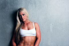 Young blonde fitness woman. Attractive fitness woman with a toned body standing with her back to a wall with her arms by her side Stock Images