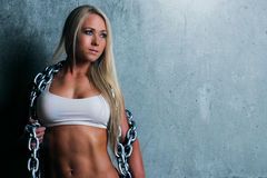 Young blonde fitness woman. Attractive fitness woman with a toned body standing with her back to a wall looking away from the camera, holding a metal chain Stock Photos