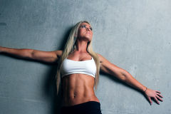 Young blonde fitness woman. Attractive fitness woman with a toned body standing with her back to a wall looking up Royalty Free Stock Image