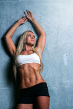 Young blonde fitness woman. Attractive fitness woman with a toned body standing with her back to a wall looking up, holding her arms above her head Royalty Free Stock Image