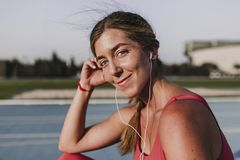 Young blonde fitness woman runner relaxing on stadium blue track at sunset listening to music on headphones an mobile phone Sport royalty free stock image