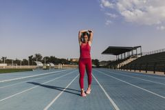 Young blonde fitness woman runner stretching arms on stadium blue track at sunset. Sport and healthy lifestyle concept royalty free stock photos