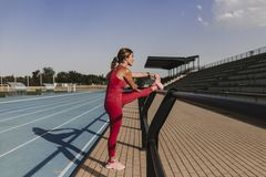 Young blonde fitness woman runner stretching legs on stadium blue track at sunset. Sport and healthy lifestyle concept royalty free stock photo
