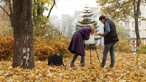 Young girl artist teaching a sudent how to draw in the autumn park. Young blonde girl artist in the purple coat teaching a sudent how to draw a picture on the royalty free stock photos