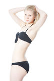 Young blonde girl in a black bikini Royalty Free Stock Photo