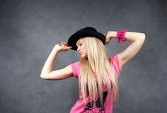 Young blonde girl in black hat Stock Images