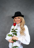 Young blonde girl in a black hat with a Royalty Free Stock Images