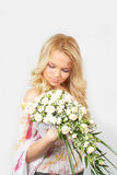 Young blonde girl with a bouquet of flow Royalty Free Stock Images