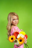 Young blonde girl with a bouquet of flow. Beautiful young blonde girl with a bouquet of flowers Royalty Free Stock Photos