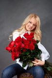 Young blonde girl with a bouquet of rose Stock Photos