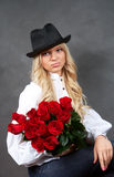 Young blonde girl with a bouquet of rose Stock Photography