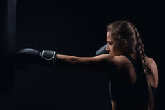 Young blonde girl in boxing gloves pushes the bag. Young girl in boxing gloves pushes the bag on a black background Royalty Free Stock Image