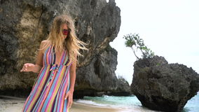 Young blonde girl in a bright dress runs along the white beach, smiling at the camera, developing hair. stock footage