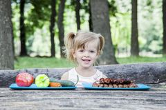 Young blonde girl choosing food for her meal royalty free stock images