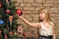 Young blonde girl and Christmas tree Stock Image