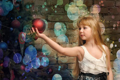 Young blonde girl and Christmas tree Royalty Free Stock Photos
