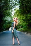 Young blonde girl dancing on the road royalty free stock photos