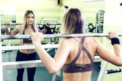 Young blonde girl doing exercises with barbbell in a GYM. Strong woman, healthy lifestyle, losing weight concept Royalty Free Stock Photography