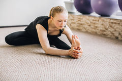 Young blonde girl doing stretching exercises. Yoga class Stock Image
