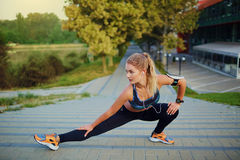 Young blonde girl doing warm-up in park on summer autumn nature. Stock Photos