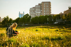 Young blonde girl in dress with shoulder bag, walking on dandelion field royalty free stock photo