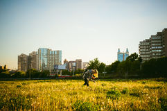 Young blonde girl in dress with shoulder bag, walking on dandelion field stock photo