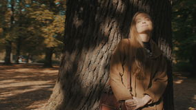 Young blonde girl enjoying beautiful day in sunny autumnal park. Outdoors portrait of happy young woman standing in autumn park under a tree stock footage