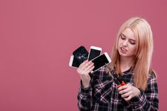 A girl, holds several smartphones and breaks them with a clasp. On a pink background. A young blonde girl, of European appearance, holds several different stock photos